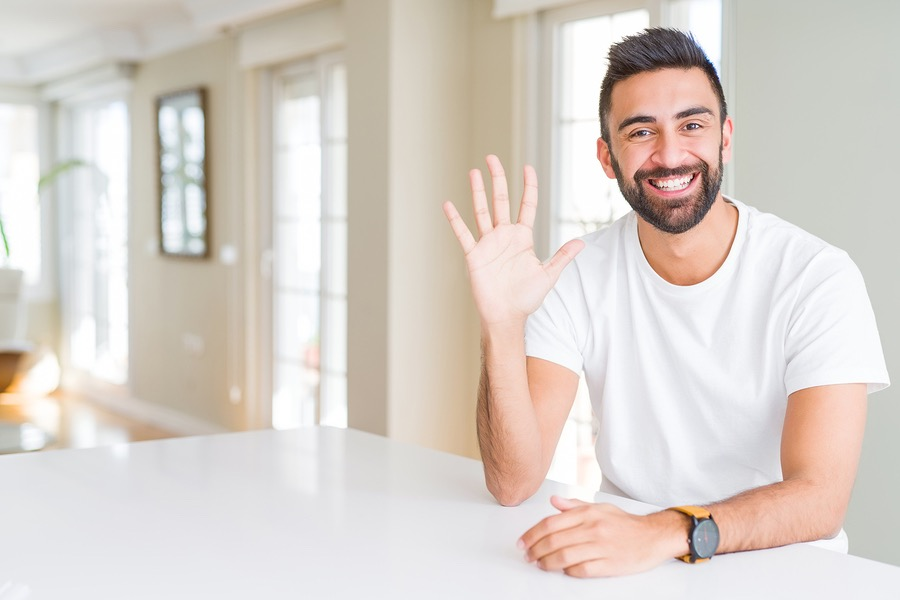 Handsome hispanic man casual white t-shirt at home showing and pointing up with fingers number five while smiling confident and happy.