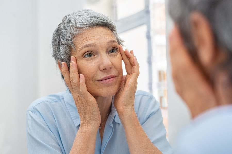Senior woman looking in mirror after taking Hyalogic® Hylavision