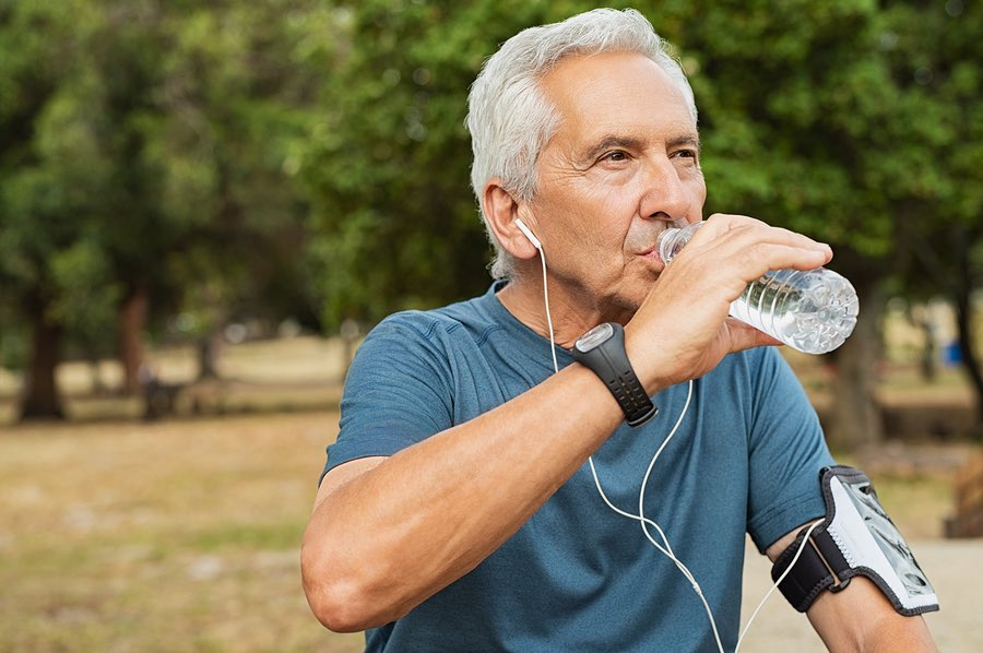 Senior man drinking water and Hyalogic® Hyaluronic Acid after a workout