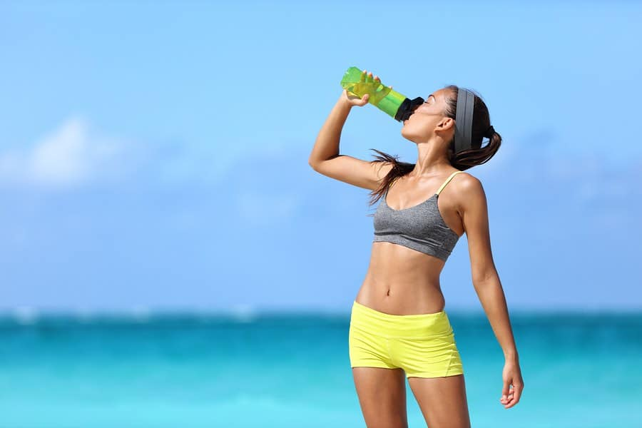 Woman drinking water, hydrating on a beach. From Hyalogic®