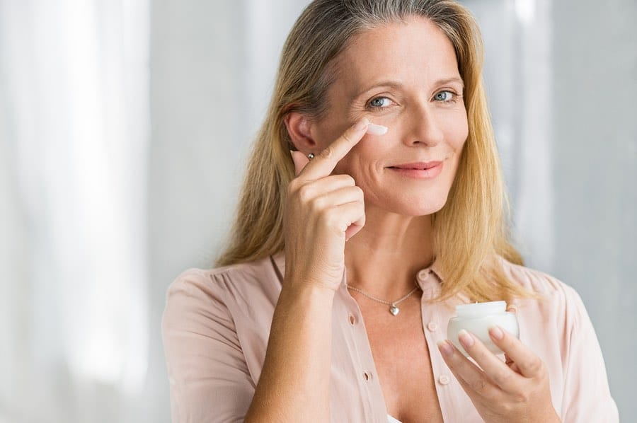 Smiling senior woman applying Hyalogic® anti-aging lotion