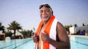 Older man smiling by swimming pool
