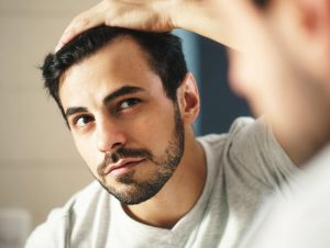 Man looking at hair in Mirror after using Hyalogic Biotin Mist