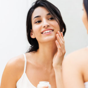 woman applying Hyalogic hyaluronic acid product to her face